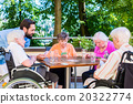 Group of seniors and nurse playing cards  20322774