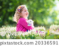 Little girl playing with bunny on Easter egg hunt 20336591