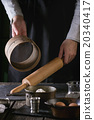 Female hands with wooden rolling-pin and sieve 20340417