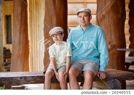 Happy father with son talking and having rest 20340555