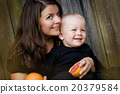 Mother and son eating orange 20379584