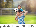 Father and son playing football 20380059