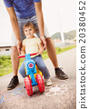 Father and daughter on motorbike in park 20380452