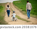 Family with little boy on tricycle in nature 20381076