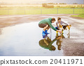 Young couple walk dog in rain 20411971