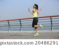 young fitness woman jumping rope at seaside 20486291