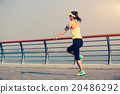 young fitness woman jumping rope at seaside 20486292