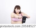 흰색 배경 앞에서 진지한 표정으로 체지방 측정기 체지방을 정하고있다 살찐 젊은 여자 20568527