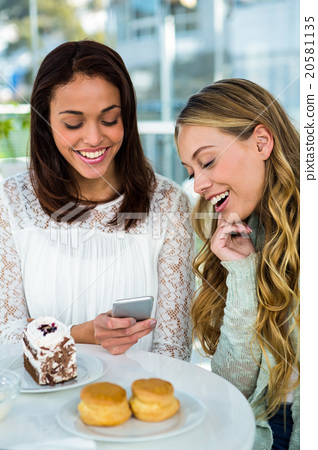 two girls watch a phone 20581135