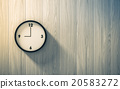 Black clock hanging on the wood wall 20583272