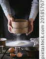 Sifting flour by female hands 20585767