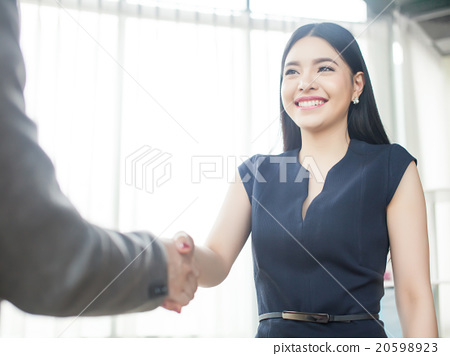 Stock Photo: Smart Asian woman smiling and shaking hand