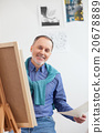 Cheerful senior painter is drawing the image 20678889
