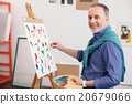 Experienced mature painter is working in his 20679066