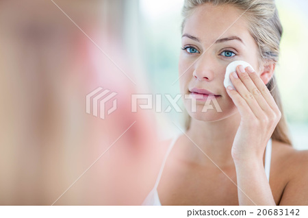 Stock Photo: Woman wiping her face with cotton pad