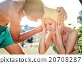 Man helping woman in bikini with heatstroke 20708287
