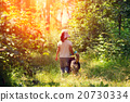 Little girl walking with dog in the forest 20730334