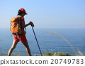 young woman backpacker walking on seaside mountain trail 20749783