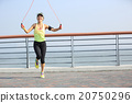 young fitness woman jumping rope at seaside 20750296