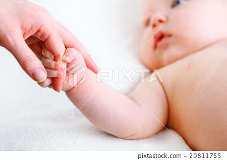 Stock Photo: concept of parental love. baby hand holding finger of mother