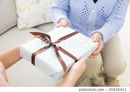시니어 여자에게 선물을 전달 젊은 여성 20836411