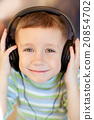 the child listens to music via earphones 20854702