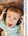 the child listens to music via earphones 20854703