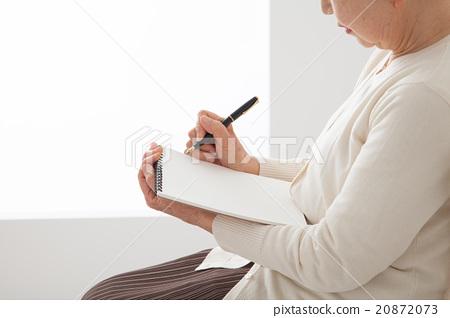 坐在椅子上和寫作筆記高級女性結束筆記我自己的歷史 20872073