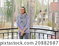 attractive lady in sweater and scarf standing on balcony 20882687