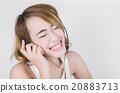 Happy Asian woman using headphone listening  20883713