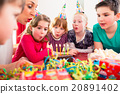 Child on birthday party blowing candles on cake 20891402