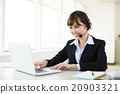 young beautiful  businesswoman with headset in office 20903321