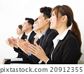 Business people sitting in a row and applauding 20912355