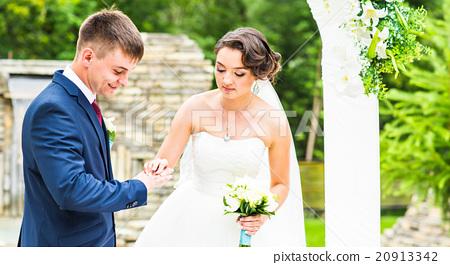 Stock Photo: Bride slipping ring on finger of groom at wedding