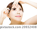young beautiful woman Applying mascara isolated on white 20932408