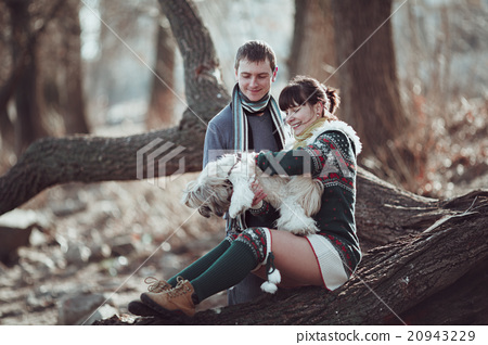 Man and woman playing with their dog at the river. 20943229