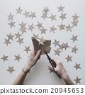 Woman's hands cut stars of craft paper 20945653