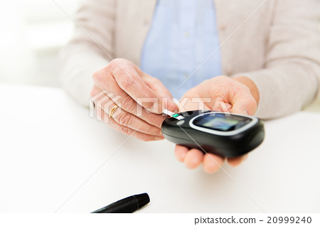 senior woman with glucometer checking blood sugar 20999240