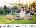 Businesswoman sitting in park working on laptop 21005957