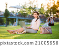 Businesswoman sitting in park working on laptop 21005958