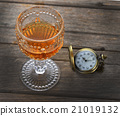 Faceted glass of whisky and Vintage pocket watch 21019132