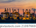 Cranes loading containers at a ship yard. 21097669
