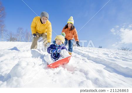스노우 파크에서 썰매 놀이를하는 3 명의 가족 21126863