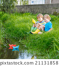 Two little brothers playing with paper boats by a 21131858