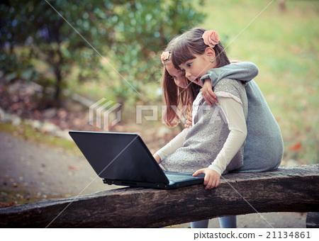 girlfriend in autumn park with laptop 21134861