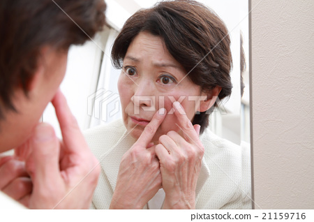 Women in their 60s who check their skin with a mirror 21159716
