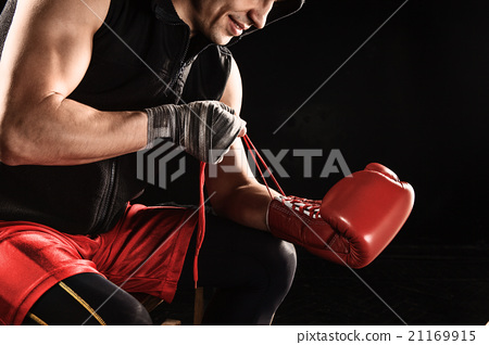 The young  man kickboxing lacing glove 21169915