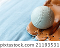 baseball in a glove on blue bed 21193531