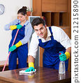 Professional cleaners in overalls with supplies 21215890
