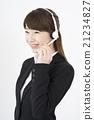接线员:年轻可爱的支持中心女人穿着西装轻轻地微笑着耳机麦克风女人的长度 21234827